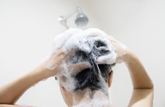 Pessoa lavando o cabelo com shampoo de babosa